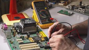 Master repairs chip. Electronics technician is testing a computer chip. PC repair stock footage