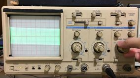 Electronics working with oscilloscope and sine wave shown on oscilloscope stock footage