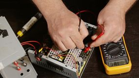Electronist using a multimeter on an electronic device, from above. Hd video stock video