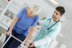Eledely lady using walking frame with help caregiver. Eledely lady using walking frame with help of caregiver royalty free stock photography