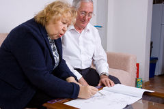Elederly couple. Mature couple at work with some plans Royalty Free Stock Photography