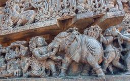 Elefant och forntida folk på bakgrund för stenvägg Mytiska platser av den 12th århundradeHoysaleshwara templet i Indien Royaltyfri Bild