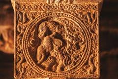 Elefant och lejon på lättnad av kolonnen som göras i det 7th århundradet av den hinduiska skulptören inom den gamla templet, Indi Arkivfoto