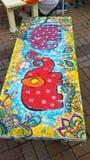 Elefanti divertenti del giocattolo dipinti su un banco, arte della via Fotografia Stock