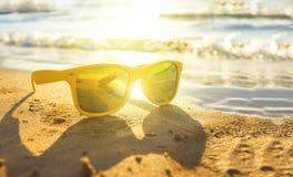 Eleganccy żółci okulary przeciwsłoneczni morzem, żółty piasek, słońce, głębia pole, plama zdjęcia stock