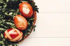 Eleganccy Easter jajka na zieleni opuszczają na białym drewnianym tle f Zdjęcie Royalty Free