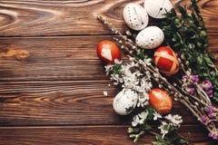 Eleganccy Easter jajka z białymi kwiatami i pączkami na drewnianym backgr Obrazy Stock