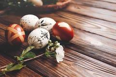 Eleganccy Easter jajka z czereśniowymi kwiatami rozgałęziają się na drewnianym backgro Zdjęcia Stock