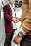 Eleganccy faceci wita each inny przy pracą podczas gdy trząść rękę obrazy stock
