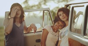 Eleganccy młodzi przyjaciele, dwa damy beside i faceta stojak retro autobus, uśmiechający się patrzeć prosto kamera 4K zdjęcie wideo