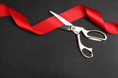 Eleganccy nożyce i czerwony faborek na czarnym, mieszkanie kłaść z przestrzenią dla teksta Ceremonialny taśmy rozcięcie zdjęcia stock