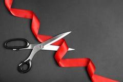 Eleganccy nożyce i czerwony faborek na czarnym tle, mieszkanie nieatutowy Ceremonialny taśmy rozcięcie zdjęcie stock