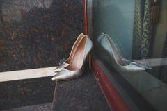 Eleganccy panna młoda ślubu buty na nadokiennym tle Fotografia Royalty Free