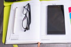 Eleganccy szkła kłama blisko telefonu komórkowego na laptopu stole Zdjęcie Stock