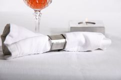 Elegance. Dinner party place setting featuring only a candle, napkin and wine glass set on linen tablecloth Stock Photo
