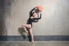 Elegance ballerina holding gift box above head royalty free stock photos