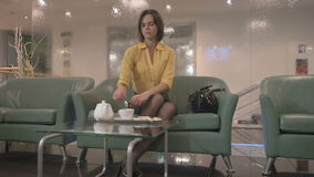 Elegance brunette drinks tea on the sofa stock video footage