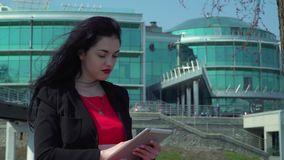 Elegance brunette with red lips using digital tablet near the office center. Beautiful elegant woman wearing red dress using herdigital tablet at office center stock footage