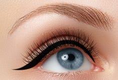 Elegance close-up of beautiful female eye with fashion eyeshadow. And eyeliner. Macro shot of woman`s beautiful blue eye with extremely long eyelashes. Sexy Stock Photography