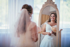 Elegance cute bride holding a bouquet looks in the mirror Stock Photography