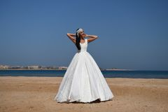 Elegance and fashion model. Bride and wedding ceremony. Woman in white dress. Wedding fashion and beauty salon.Girl in dress on blue sky at sea Royalty Free Stock Photo