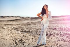 Elegance and fashion model. Bride and wedding ceremony. Woman in white dress in sand dunes. Wedding fashion and beauty salon. Girl in dress in sunny desert Royalty Free Stock Image