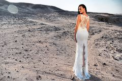 Elegance and fashion model. Wedding fashion and beauty salon. Woman in white dress in sand dunes. Girl in dress in sunny desert. Bride and wedding ceremony Stock Images