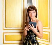Elegance fashion woman reading ebook. Tablet in golden door Royalty Free Stock Photos
