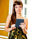 Elegance fashion woman reading ebook tablet. In golden door Stock Photo