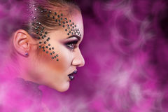 Elegance female in studio with multicolored smoke Royalty Free Stock Image