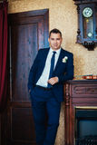 Elegance groom  is posing on the background room Royalty Free Stock Photo