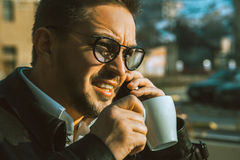 Elegance male talking phone and drink coffee. Outdoors Royalty Free Stock Photography