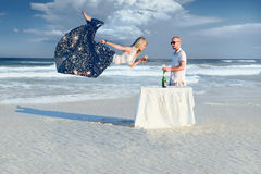 Elegance man in sunglasses and young flying blonde girl Stock Photos