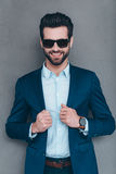 Elegance and masculinity. Cheerful young handsome man in sunglasses keeping hand on his jacket and looking at camera with smile while standing against grey Royalty Free Stock Photos