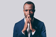 Elegance and masculinity. Portrait of thoughtful young African man in smart casual jacket holding hand clasped near face and looking at camera while standing Royalty Free Stock Images