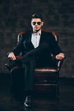 Elegance and masculinity. Young handsome man in suit and sunglasses holding hand on chin and looking at camera while sitting in leather chair against dark grey Stock Photos