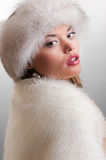 Elegance model in fur. Elegance model in white fur posing against grey background royalty free stock photography
