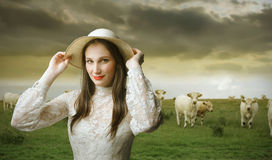 Elegance in nature. Beautiful woman with hat standing on a green meadow with some cows on the background Royalty Free Stock Photos