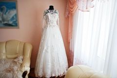 Elegance rich wedding dress on mannequin near the window. Royalty Free Stock Photo