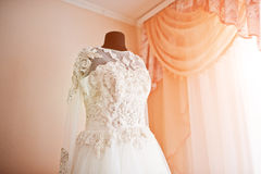 Elegance rich wedding dress on mannequin near the window. Stock Photos