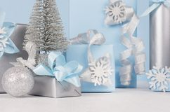 Elegance soft christmas home decorations - silver small fir with blue and metallic gift boxes with shiny ribbons and snowflakes. Elegance soft christmas home royalty free stock photography