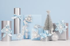 Elegance soft christmas home decorations - silver small fir with blue and metallic gift boxes with shiny ribbons and snowflakes. Elegance soft christmas home royalty free stock photo