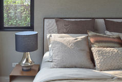 Elegance style pillows setting on classic style bedding and reading lamp Stock Photography