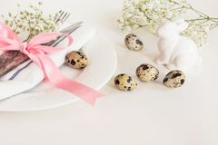 Elegance table setting with pink ribbon and flower on white background. Easter romantic dinner. Top view and copy space Stock Image