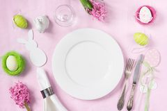 Easter romantic dinner. Elegance table setting spring pink flowers on pink linen tablecloth. Top view. Elegance table setting spring pink hyacinth flowers on Royalty Free Stock Photos