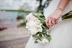 Elegance white wedding bouquet at hand of bride.  Stock Photos