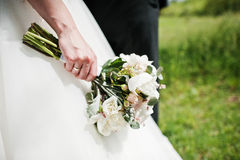Elegance white wedding bouquet at hand of bride.  Royalty Free Stock Images