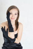 Elegance woman in black gloves and dress on light baclground. Elegance woman in black gloves and dress Royalty Free Stock Photography