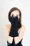 Elegance woman in black gloves and dress on light baclground. Fear Stock Photography