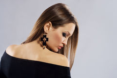 Elegance woman with cross shape earring Royalty Free Stock Photos